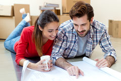 Young couple looking at the blueprints of their new home. Portrait of Young couple looking at the blueprints of their new home Royalty Free Stock Images