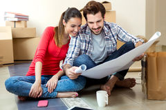 Young couple looking at the blueprints of their new home Stock Images