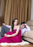 Young couple looking at the camera in their room. Young couple sitting on the floor and looking at the camera Royalty Free Stock Photos
