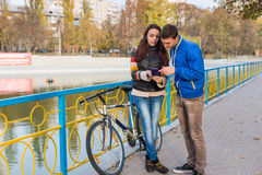 Young Couple Looking at Cell Phone in Park Royalty Free Stock Photos