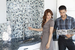 Young couple looking at color samples together in contemporary kitchen Royalty Free Stock Images