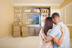 Young Couple Looking At Drawing of Entertainment Unit In Room. Young Military Couple Looking At Drawing of Entertainment Unit In Room With Moving Boxes Royalty Free Stock Image