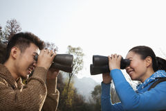 Young couple looking at each other through binoculars Stock Photography