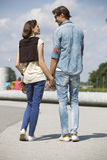 Young couple looking at each other while holding hands on street Stock Image