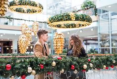 A young couple looking at each other in shopping center at Christmas. Stock Images