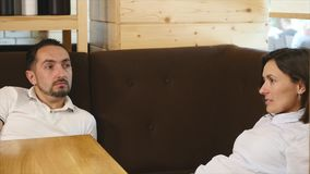 Young couple looking at each other and smiling while sitting in a cafe stock video
