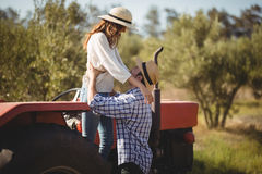 Young couple looking at each other while standing by tractor Stock Image