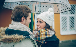 Young couple looking at each other under umbrella Royalty Free Stock Images