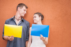 Young couple looking into eyes and holding frames background Royalty Free Stock Images