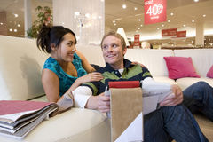 Young couple looking at fabric samples in shop, woman on sofa, smiling Stock Photography