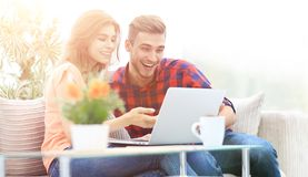 Young couple looking at a laptop screen. While sitting in a modern living room Royalty Free Stock Photography