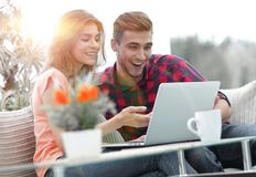 Young couple looking at a laptop screen. While sitting in a modern living room Royalty Free Stock Photos