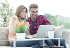 Young couple looking at a laptop screen. While sitting in a modern living room Royalty Free Stock Images