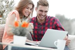 Young couple looking at a laptop screen. While sitting in a modern living room Stock Photos