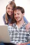 Young Couple Looking At Laptop Together. Couple Looking At Laptop Together Stock Photo