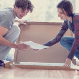 Young couple looking at manual of self assembly furniture Stock Photography