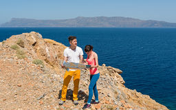A young couple looking at the map near the sea Stock Photo