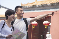 Young couple looking at map and pointing. Royalty Free Stock Photos