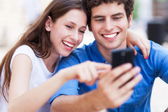 Young couple looking at mobile phone. Young people with mobile phone smiling Royalty Free Stock Photography