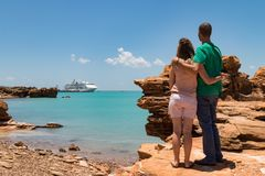 Young couple looking at modern cruise ship tied up to jetty. Royalty Free Stock Photos