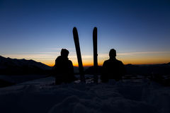 Young couple looking at the mountain sunset. Two young people looking at the mountain sunset with skis Stock Photography