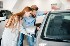 Young couple looking at new car in showroom Royalty Free Stock Image