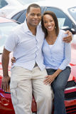 Young couple looking at new cars. On lot Royalty Free Stock Photography