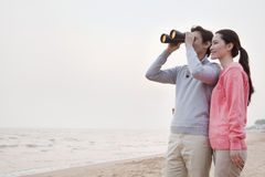 Young Couple Looking at the Ocean with Binoculars Stock Photos
