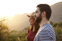Young couple looking out over mountains. Young couple looking out surrounded by bushes and very bright sun to their left wearing t-shirts and a straw hat at Stock Photography