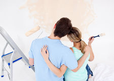 Young couple looking at a painted wall. In their new house Stock Photo