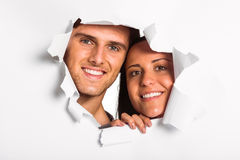 Young couple looking through paper rip Stock Image