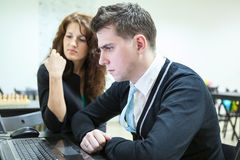 Young couple looking at pc screen with serious look Royalty Free Stock Photos