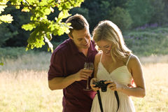 A young couple looking at photographs on their camera Stock Photography