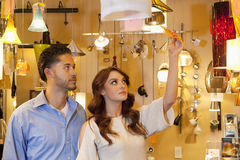 Young couple looking at price tag of lighting equipment in lights store Royalty Free Stock Photo