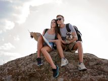 Beautiful young couple sitting on the rock and looking at the map royalty free stock photography