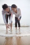 Young couple looking at seashells on the beach Stock Photography