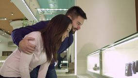 Couple looks at the shopping display with jewelry at the shop. Young couple looking at the shopping display with jewelry at the shop. Handsome bearded men Royalty Free Stock Image