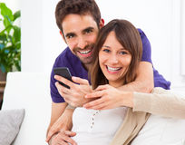 Young couple looking a smartphone at home Stock Photography