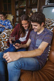 Young couple looking smartphone sitting on sofa Stock Photography