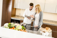 Young couple looking tablet in the kitchen while preparing mea Stock Photo