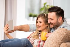 Young couple looking at tablet and laughing at home Royalty Free Stock Photography