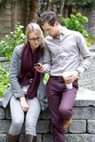 Young Couple Looking At Their Smartphone royalty free stock photo