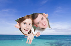 Young couple looking though hole at tropical sea Royalty Free Stock Image