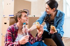 Young couple looking tired while eating a sandwich during renovation royalty free stock photo