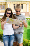 Young couple looking at tourist map. Attractive casual young couple in sunglasses standing close together looking at a tourist map on their summer vacation Royalty Free Stock Photos