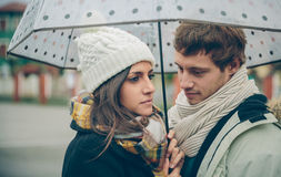 Young couple looking under umbrella in a rainy day Stock Images