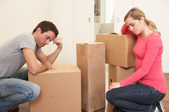 Young couple looking upset among boxes Royalty Free Stock Photo