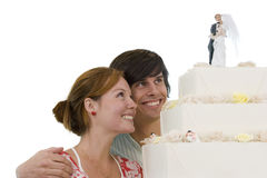 Young couple looking at wedding cake, smiling, cut out stock photo