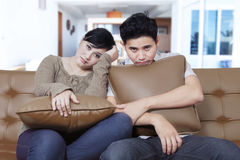Young couple looks bored on the sofa Royalty Free Stock Images