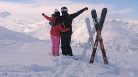Young couple looks at a mountain view and waves their hands. An active skiing couple outdoors in mountains stands on the peak, enjoying a beautiful winter view stock video footage